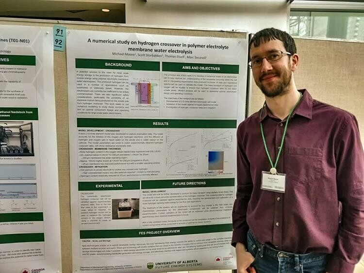 Michael stands in front of his research poster