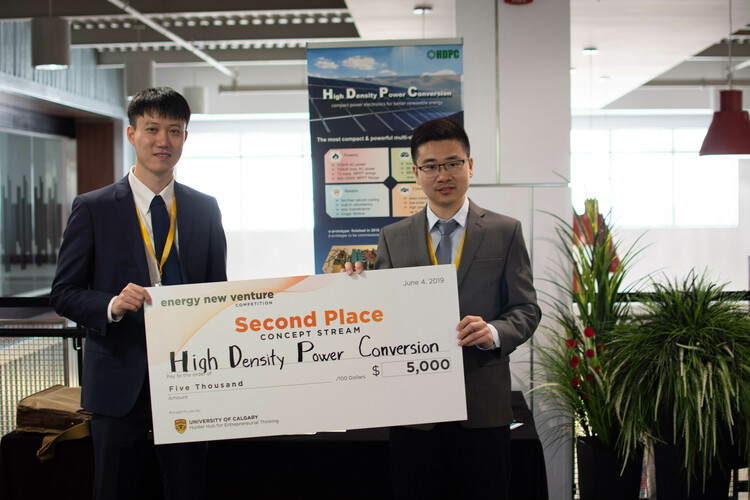 Zhongyi and colleague stand with their prize for their technology at a competition.