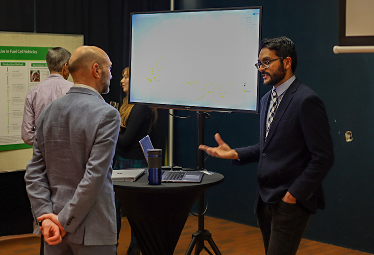 Sonak talks with a man in front of a screen displaying the Canadian Renewable Energy Project map.